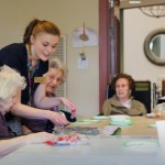 Jen Cross, Community Life Assistant, leads an interactive group art project with residents.