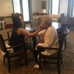Volunteer Stefanie gives an Assisted Living resident a soft new look in a complimentary make up session.
