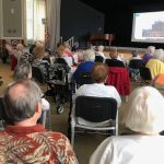 A large group of residents enjoying the slide show presentation